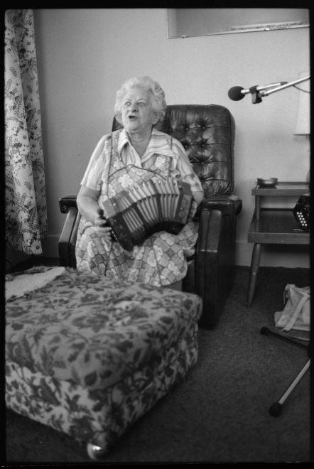Image of Mae Mulcahy singing and playing concertina in living room on armchair.