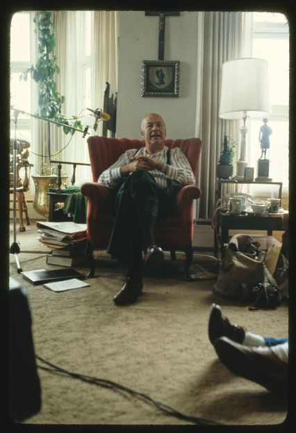 Image of Father O'Sullivan sitting in armchair  surrounded by scrapbooks.