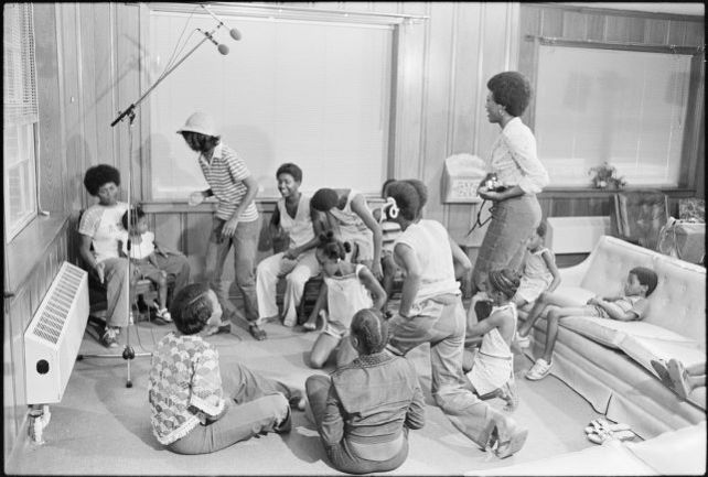 A dozen school children in a loose circle play hand games in a room. A microphone stand and two microphones are visible in the corner.