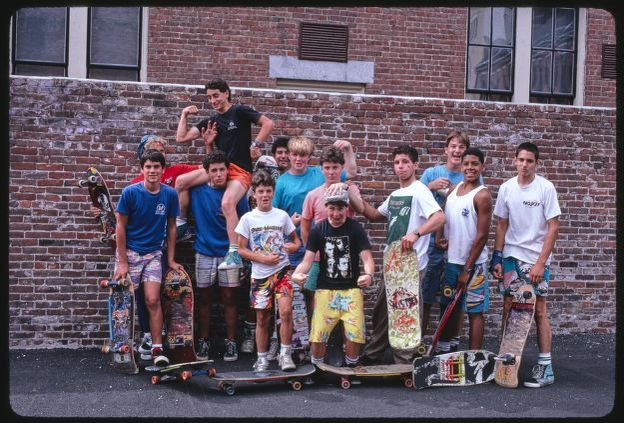 A group of young boys with skateboards poses in front of a brick wall in a parking lot.