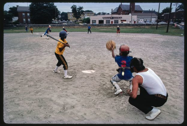 Image of little league baseball game, shot from behind umpire. Catcher has glove open and batter appears ready to swing at the ball.