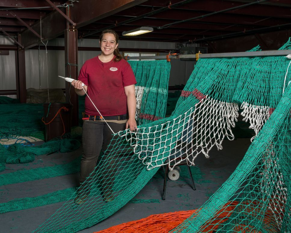 Woman stands next to a large fishing net that she is repairing.
