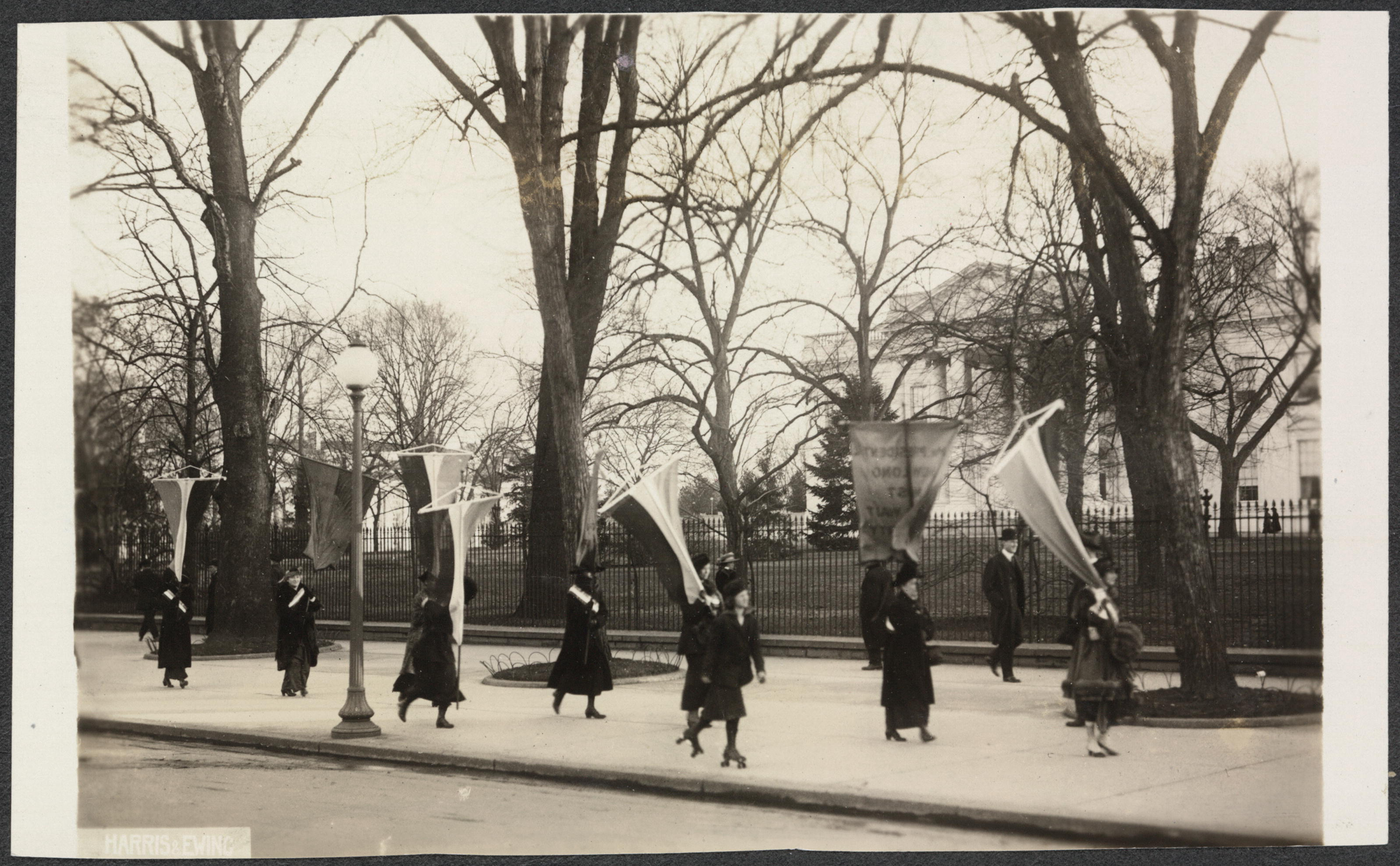 Image: Photograph of suffragists marching in contingent with banners, picketing outside on the sidewalk in front of the White House. A woman skates by in foreground on roller skates, and a man in bowler hat strolls down sidewalk near fence, 1917.