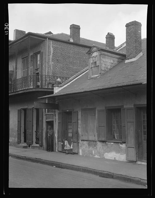 View from across street of two children standing in a doorway in the French Quarter, New Orleans