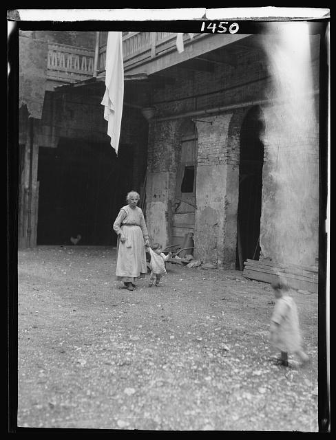 Woman and children in a courtyard, New Orleans