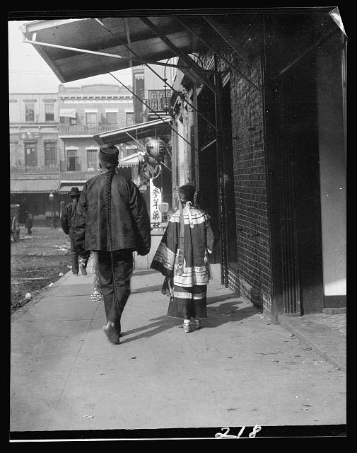 Man and a young girl walking down a sidewalk, Chinatown, San Francisco