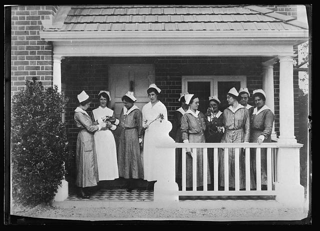 "Amer. Nurses on the porch of their Red Cross Club house on the banks of the River Test, Somewhere-in-England. ""I don't know why they should call it a river,"" the newly arrived nurse invariably remarks, for is seems too small to be dignified by any name more ambitious than ""creek"", but they learn to like as they grow more familiar with it. The Nurses' Club, built up close to the Amer. Hospital, is an unpretentious little building of cottage type, but cozy and comfortable, with pleasant dining rooms and lounge rooms and reading rooms and a few bed rooms. The front yard is full of holly, which the nurses have been tending carefully in anticipation of using it at Christmas time"