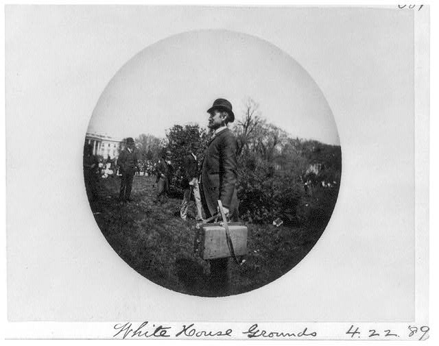 [Man with suitcase and others on the White House grounds]
