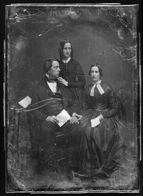 [George Perkins Marsh family. Marsh seated beside a table with tablecloth, on the left, his head turned to the right, wearing spectacles, his wife seated on the right, her hand on his, her head slightly to the left, both holding papers; Caroline's sister, Lucy Crane, standing behind and between them, her hands on her brother-in-law's shoulder, her head three-quarters to the right]
