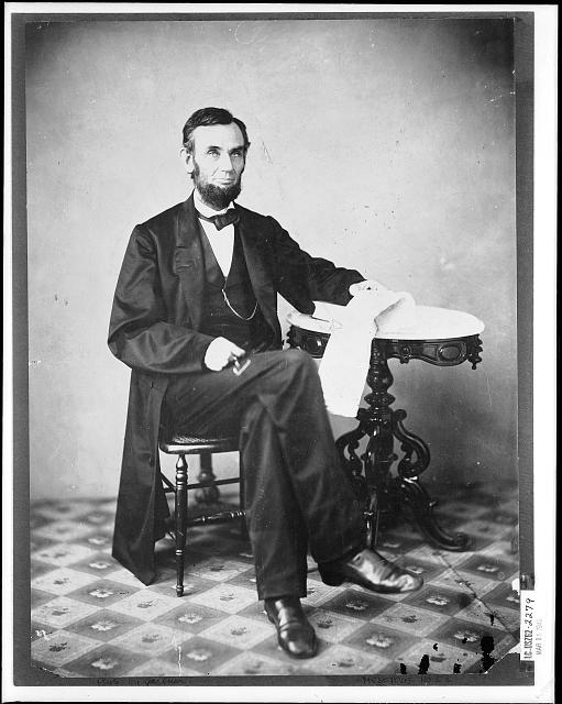 [Presidenet Abraham Lincoln, seated next to a table]