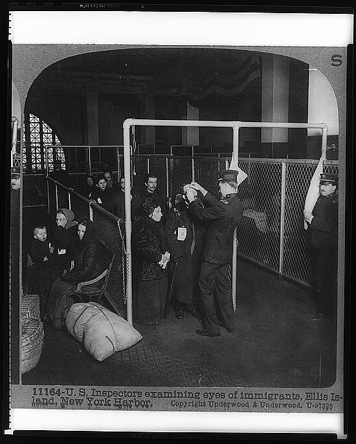 U.S. inspectors examining eyes of immigrants, Ellis Island, New York Harbor