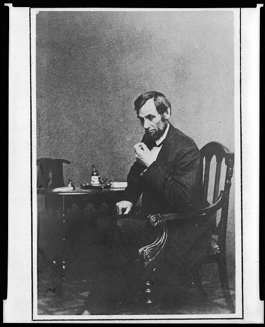 [President Abraham Lincoln, seated next to small table, in a reflective pose, May 16, 1861, with his hat visible on the table]