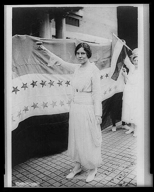 [Alice Paul, full-length portrait, standing, facing left, raising glass with right hand]