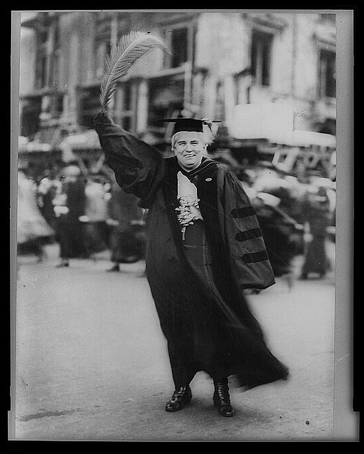 [Anna Howard Shaw, full-length portrait, standing, facing front, wearing academic robe and holding large feather]