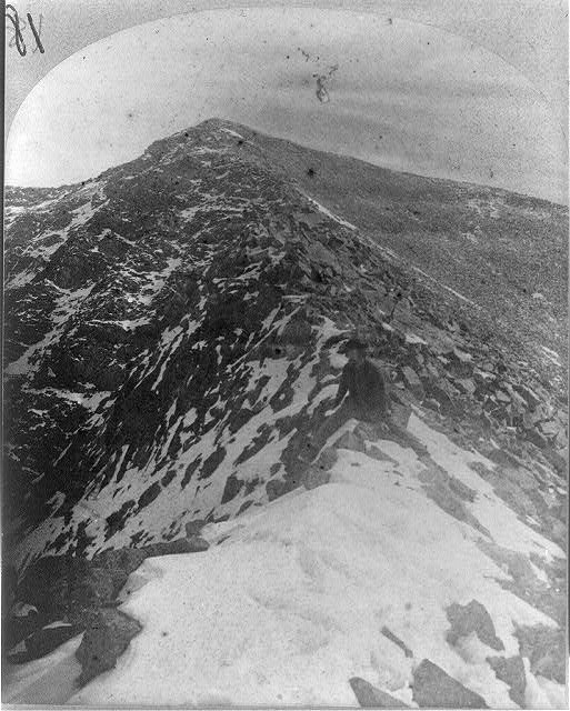 Man sitting on summit of Cerro Blanca, Colo. (north of Ft. Garland, Colo.)