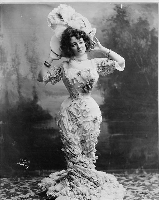 [Anna Held, full-length portrait, standing, facing front with both hands raised behind her head, wearing an ornate floral dress and hat]