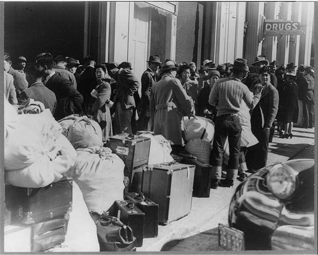 Residents of Japanese ancestry awaiting the bus at the Wartime Civil Control sta., San Francisco, Apr. 1942