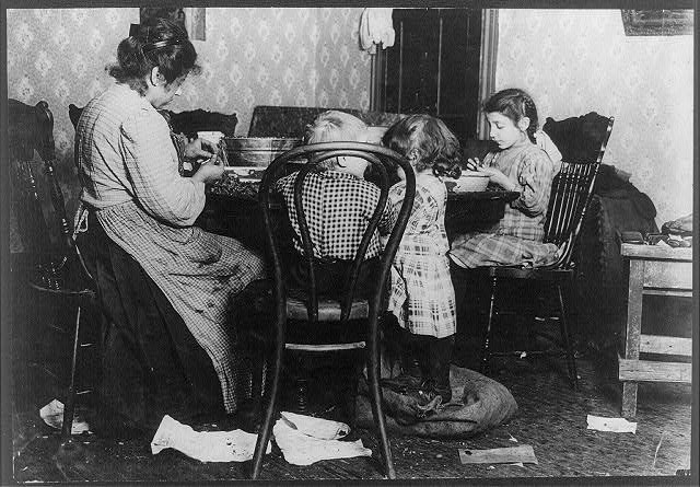Mrs. Lucy Libertine and family: Johnnie, 4 years old; Mary, 6 years; Millie, 9 [?] years, picking nuts in the basement tenement, 143 Hudson St. Mary was standing in the open mouth of the bag holding the cracked nuts (to be picked), with her dirty street shoes on, and using a huge dirty jackknife. On the right is the cobbler's bench used by shoemaker in this room. They live in dark inner bedrooms, and filth abounds in all the room and in the dark, damp entry. See 2704.  Location: New York, New York (State)