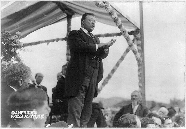 [Theodore Roosevelt speaking to a crowd from a raised platform]