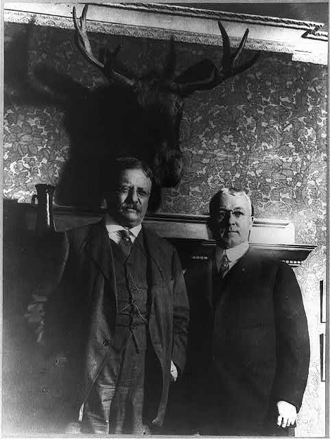"Flashlight taken of Col. Roosevelt and Professor Goode of the Chicago University, in front of a mounted moose head over Professor Goode's fireplace Roosevelt was then campaigning for the Moose Party at the time--the three original ""moose."""