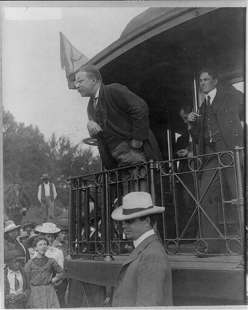 [Teddy Roosevelt speaking at the back of a railroad car]