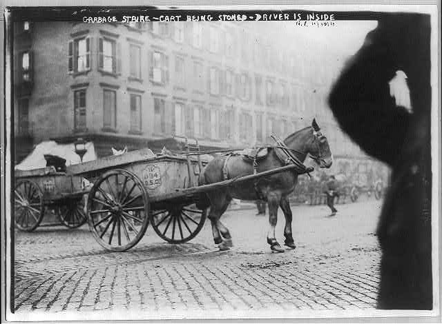 [N.Y.C. Garbage collector's strike, 1911: horse-drawn cart being stoned; driver is hiding inside]