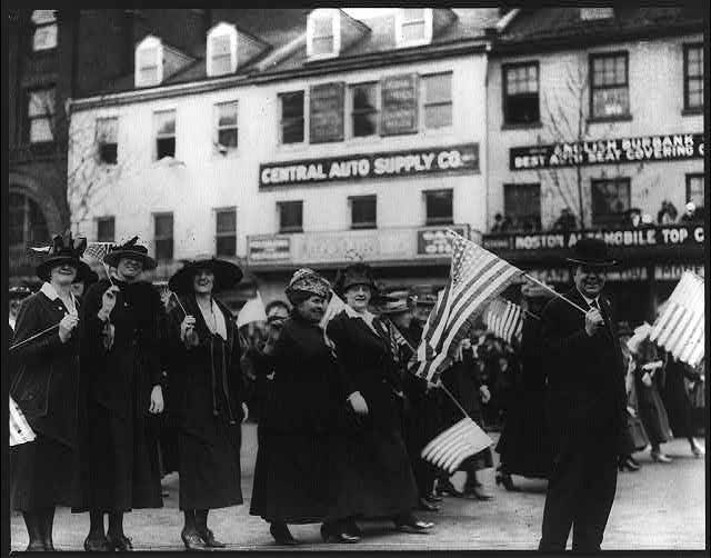 [Liberty Bond drive, 1918 - man and women with U.S. flags marching in parade, 1000 block of Pennsylvania Ave, Washington, D.C.]
