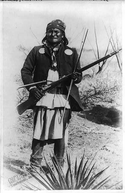 [Scene in Geronimo's camp...before surrender to General Crook, March 27, 1886:  Geronimo, full-length portrait standing, facing left, rifle at port]