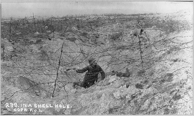 [German soldier with grenade in shell hole]