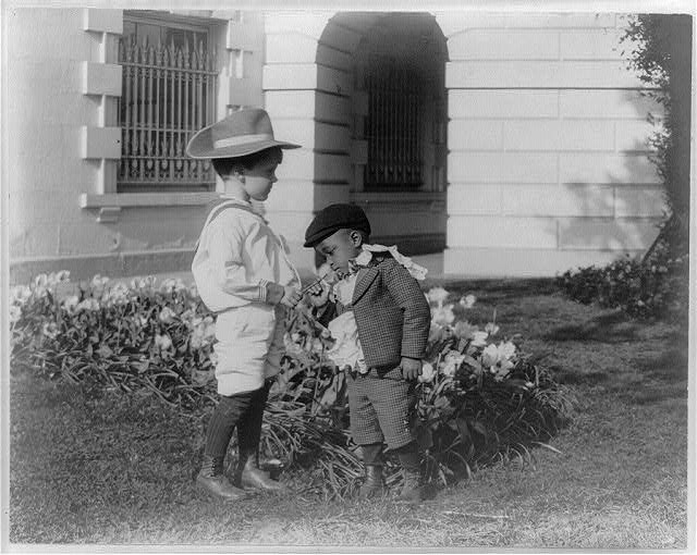 [Quentin Roosevelt as a child in front of a flower garden and Roswell Newcomb Pinckney smelling a flower at the White House, Washington, D.C.]