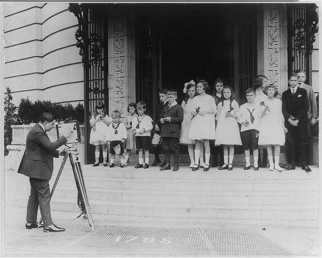 Photographer Herbert French photographing children posed at E.T. Meredith, Jr. party