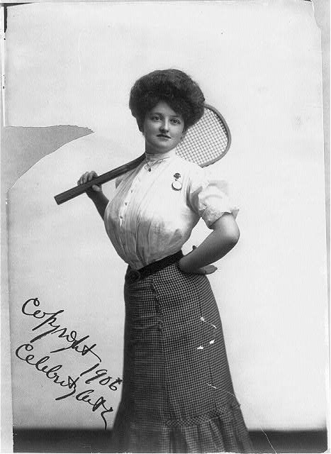 "[""Tennis Girl"" - woman posed with tennis racket on shoulder, three-quarters length, standing, facing front]"