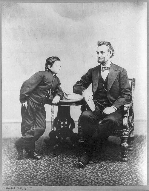 [Abraham Lincoln, seated and holding a book, with his son Tad (Thomas) leaning on a table]