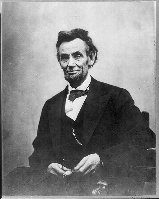 [Abraham Lincoln, three-quarter length portrait, seated and holding his spectacles and pencil (retouched to stand out)]