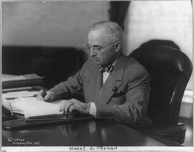 [Harry S. Truman. Bust portrait, seated at desk, with pen and papers in hand, facing left]