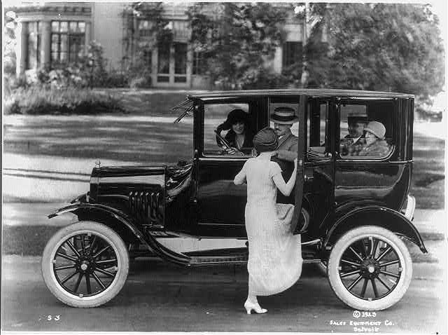 [Side view of a Ford sedan with four passengers and a woman getting in on the driver's side]