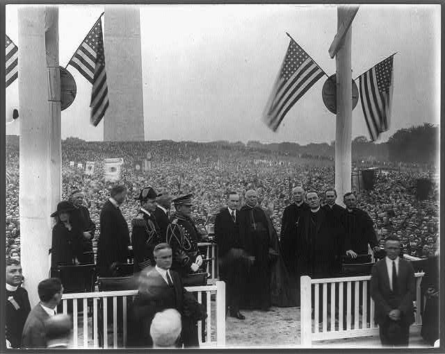 [President Coolidge on speaker's stand with Army and Navy officers, and 5 Catholic priests; Washington Monument in background and large crowd on Monument grounds]