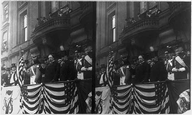 [William H. Taft, Pres. U.S., half-length portrait, standing on platform, facing left; with others; tipping hat]