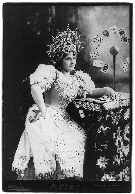 "[Lillian Russell, 1861-1922, three-quarters length, seated, facing right; with cards at table, in the ""Tzigane"" (fortune teller)]"