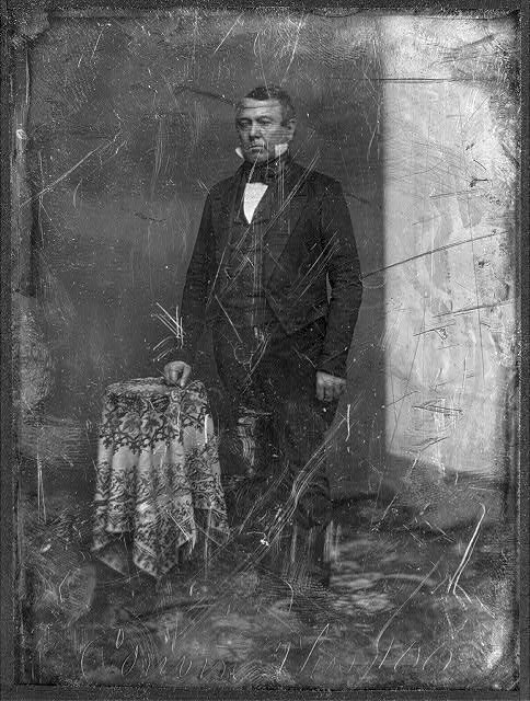 [Thomas Corwin, full-length portrait, three-quarters to the left, standing by table with tablecloth, backdrop or reflector screen prominent on left]