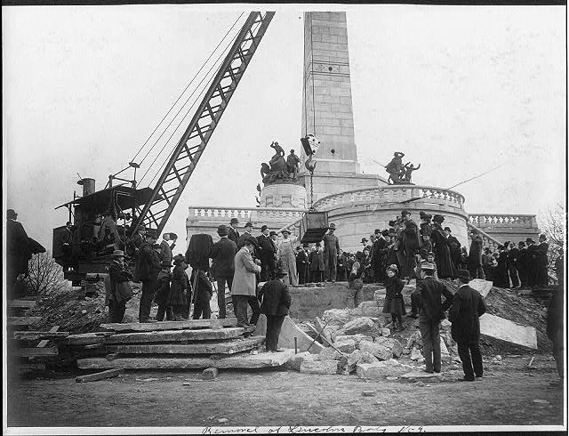 [Large crowd watching crane lift box containing Abraham Lincoln's body above grave in front of Lincoln Memorial at Springfield, Ill.]