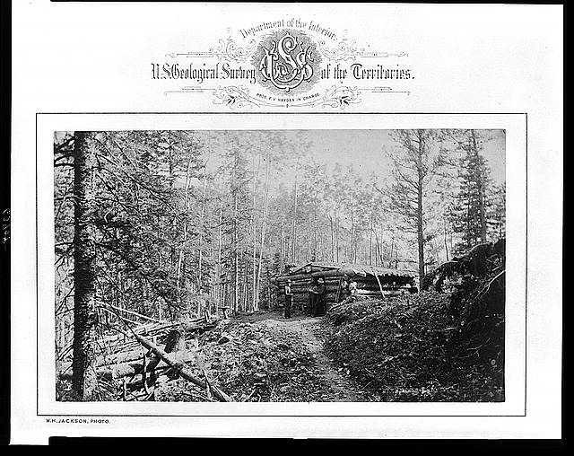 [Three men standing in front of log cabin at camp for U.S. Geological Survey team, Rocky Mountains]