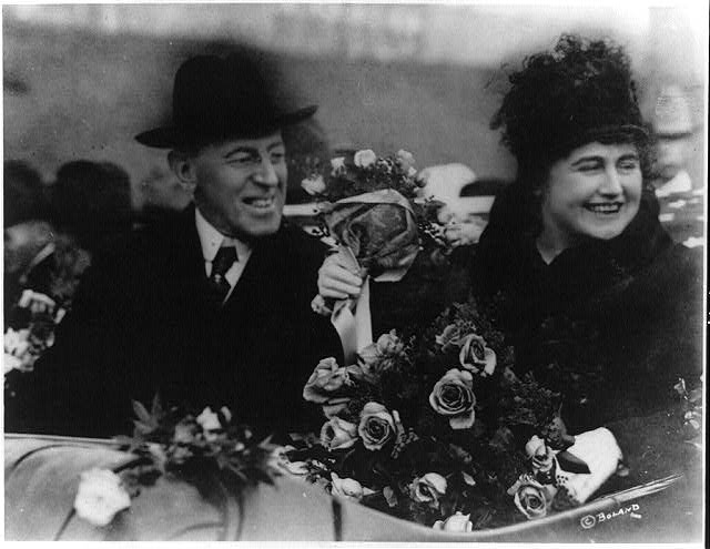 President Wilson and Edith Galt pictured smiling while riding in car decorated with flowers.
