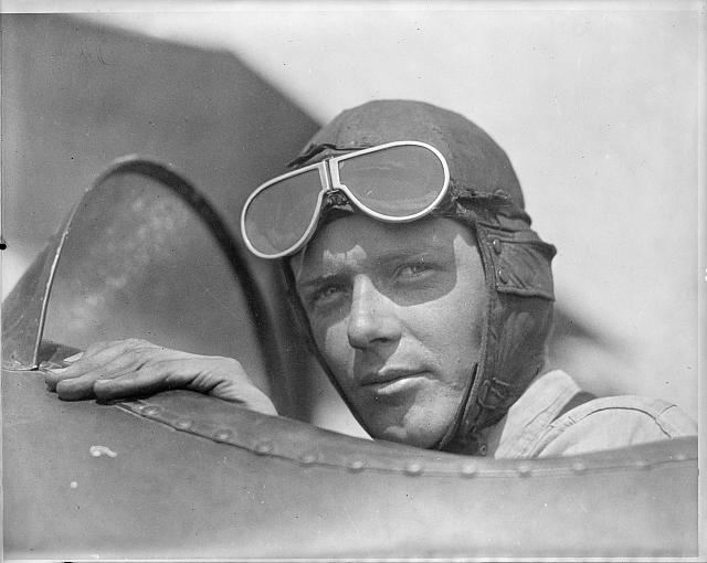 [Charles Lindbergh, wearing helmet with goggles up, in open cockpit of airplane at Lambert Field, St. Louis, Missouri]