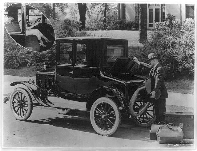 [Man loading luggage into the trunk of a Ford coupe; insert of a woman seated behind steering wheel]
