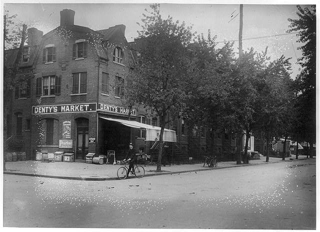 [View of H Street, N.W., North side, looking East from 6th Street showing a man on bicycle in front of Denty's Market on the corner]