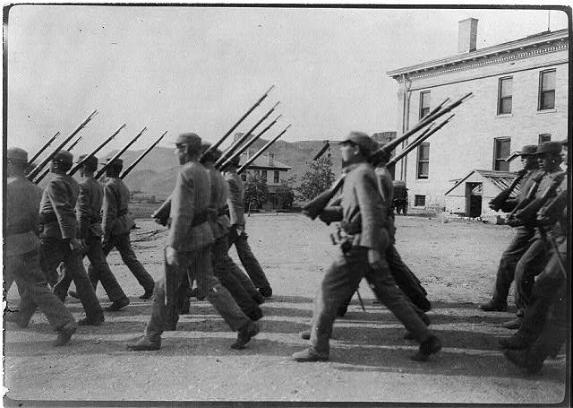 [Boys at drill (marching), Golden Industrial School, Denver, Colorado: Side view of boys marching in foreground]