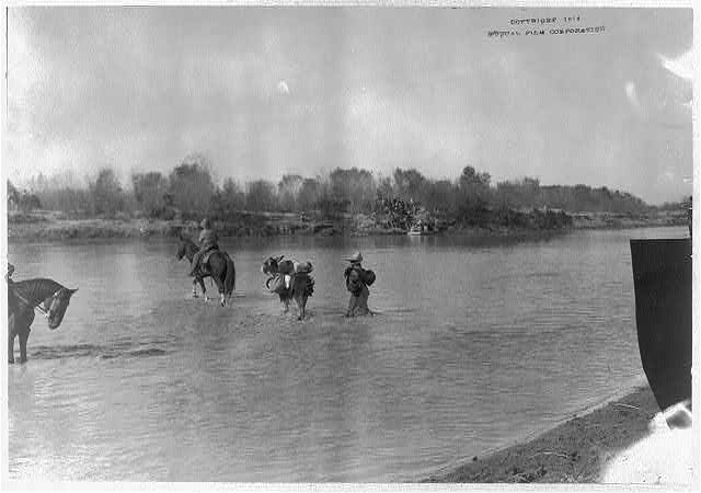[Mexican War, 1914: refugees crossing (Rio Grande?) river by horse]