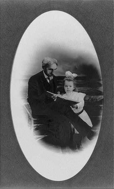 [William Henry Werner, full-length portrait, seated, looking at a book with his grand daughter]