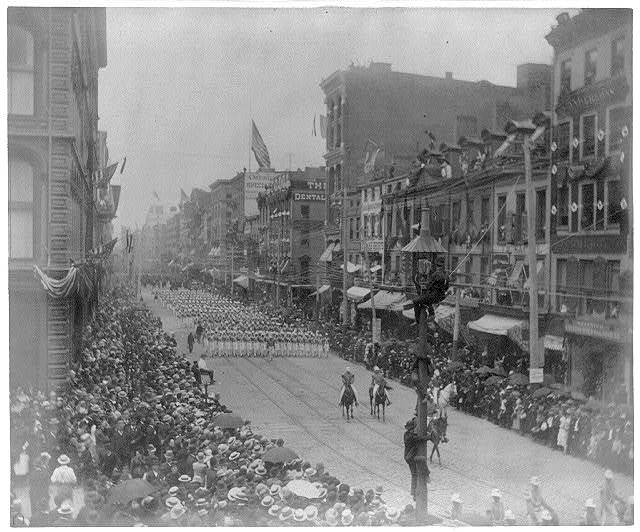 [Funeral of Pres. Grant, New York City: groups of men marching in backgrd.; 3 men in light pole in foregrd.]